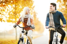 Beautiful day in the park, two young people riding bikes.